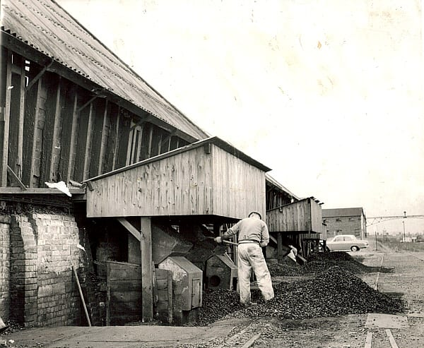 6. Shovelling the coal into the fires that supplied heat through the flues under the Pan. Murgatroyd's.jpg